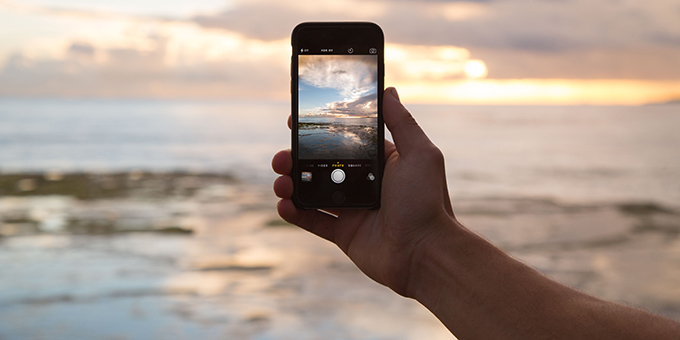 man's forearm taking picture of horizon with smart phone